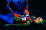 Fototapety Concept. DJ playing at the club. Girl painted in UV powder as a
