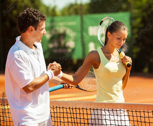 Fototapeta Young couple finish a tennis match.Shaking hands.