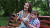 Mother and Son Blow Bubbles Sitting on a Park Bench