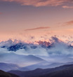 High mountain range in the clouds during sunrise. Beautiful panoramic landscape