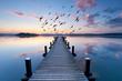 unendlich langer Holzsteg am See zur Morgendämmerung