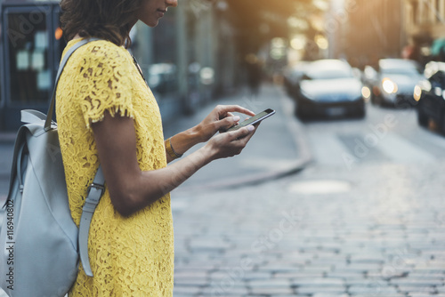 Attractive young girl walking in the city and using an app on smartphone, side view of hipster girl traveling and sending message via her cellphone, sunset in the background