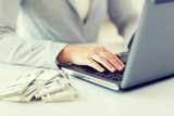 close up of woman hands with laptop and money