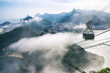 Bright misty view of the city skyline of Rio de Janeiro, Brazil with a Sugarloaf (Pao de Acucar) Mountain cable car passing in the foreground © lazyllama