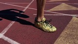 Athlete in gold shoes sprinting in slow motion on rustic red running track