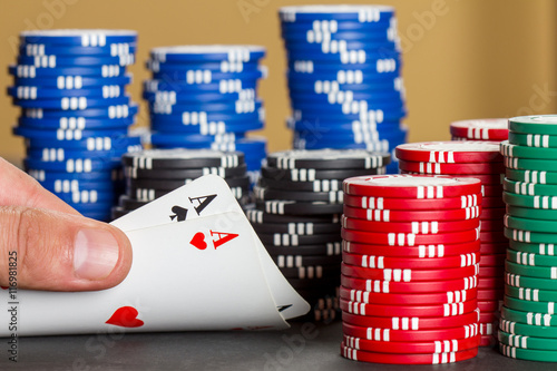 Poster Texas holdem poker game with two aces in the hand and poker chips