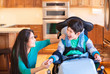 Disabled boy in wheelchair laughing with teen sister in kitchen