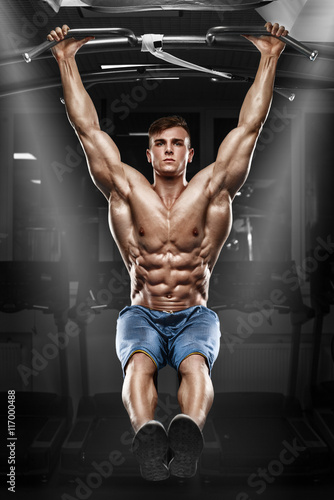 Poster Muscular man working out in gym, doing stomach exercises on a horizontal bar, st