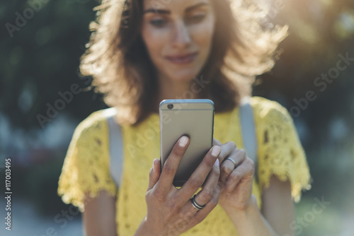 Happy smiling young girl using modern smartphone outside, beautiful woman typing text message or an sms via her cellphone while walking in the park at sunny summer day, flare light