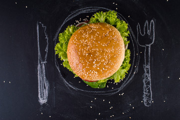 Burger with painted chalk cutlery on a black background.