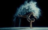 Wdzięku kobieta tańczy w chmurze pyłu