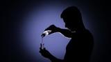 Man pouring vodka into a glass. Back light. SLow motion