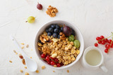 healthy granola in white bowl and summer berries