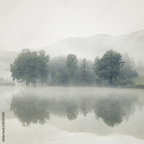 Mist on a lake at dawn with trees and mountains reflected in the - 117073082