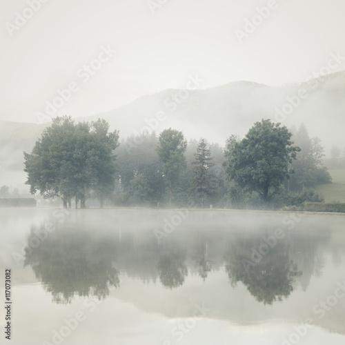 mgla-na-jeziorze-o-swicie-z-drzewami-i-gorami-odzwierciedlenie