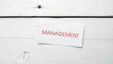 Management, the word written in red on a card, is dropped on an aged white table. Footage from a series about business related concepts.