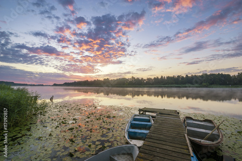 sunset over  lake,Boat anglers at a wooden pier