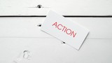 Action, the word written in red on a card, is dropped on an aged white table. Footage from a series about business related concepts.