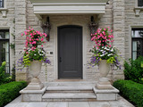 front door of stone house with large flower pots - 117121472