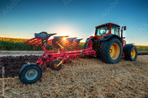 Poster Farmer in tractor preparing land with cultivator