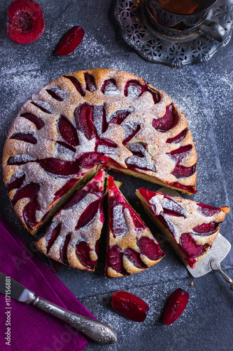 Plagát rustic plum  cake on dark background