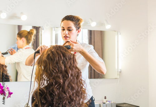 Professional hairdresser styling woman curly hair. Plakat