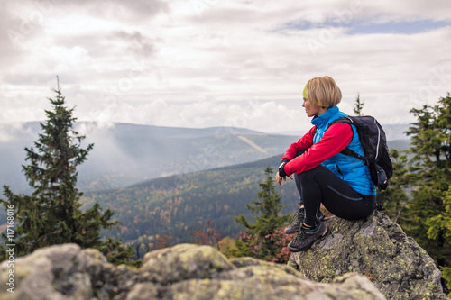 Woman hiking in autumn mountains and woods. Celebrate mountain top, inspiring recreation and healthy lifestyle outdoors in beautiful nature. Motivated backpacker blond female looking at sunset view.