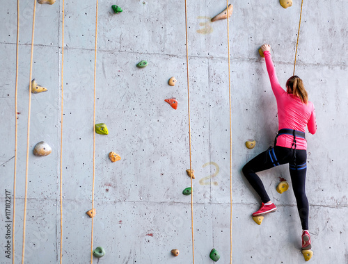 Beautiful young woman starts to climbing big artificial wall