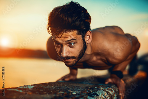 Young athletic man doing push ups outdoors Plakat