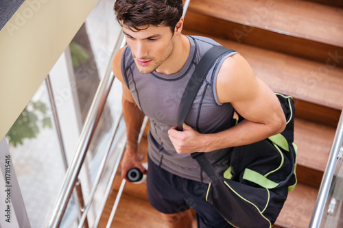 Fitness man with bag walking on stairs in gym Poster