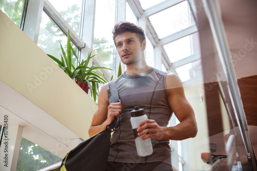 Poster Sportsman walking and drinking water after training in gym