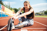 Woman athlete sitting and stretching legs on stadium