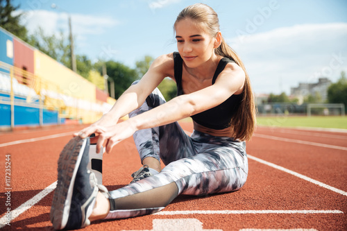 Woman athlete sitting and stretching legs on stadium Poster