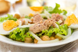 fish salad with chickpea and boiled egg on white plate