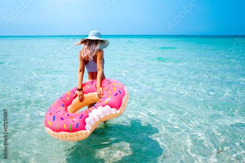 fototapeta na ścianę Woman with inflatable ring on beach