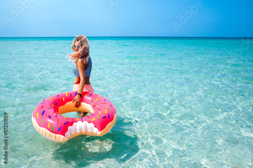 Woman with inflatable ring on beach Poster