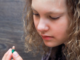The girl looks at a pill capsule with colored beads inside
