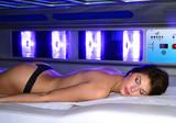 Recostada en una cama de bronceado de un salon de belleza.