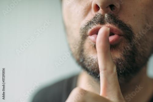 Finger on lips, man gesturing shhh sign Poster