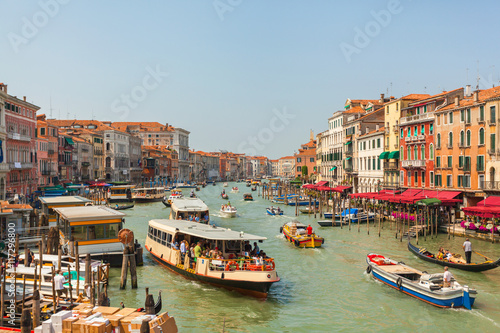 Obraz na Szkle Grand Canal in Venice in the afternoon with a lot of gondolas, boats, ferries, etc. Brightly colored houses and Palazzo of Venice with facades in different styles. Italy