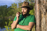 man smokes a pipe in cowboy hat