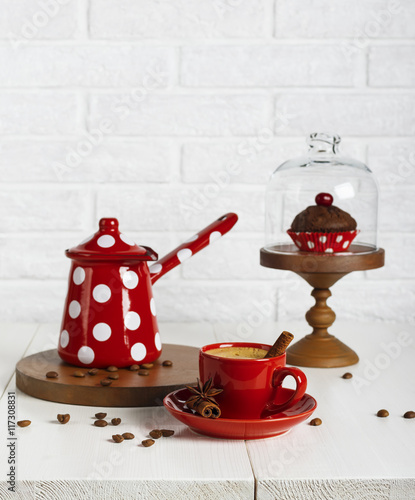 Fototapeta Red cup of coffee and coffee pot on the white table