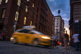 Busy street in SOHO, New York, USA with blurry people moving around and a taxi cab at sunset - 117327677