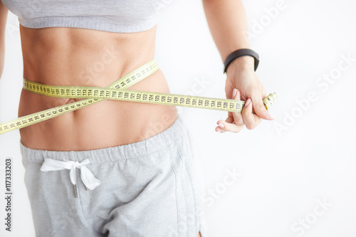 Leinwanddruck Bild Woman measuring her waistline. Perfect Slim Body