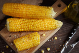 Golden corn cob with oil, herbs and salt on rustic wooden table