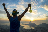 Gold medal champion athlete standing outdoors in silhouette at a golden sunrise skyline overlook in Rio de Janeiro, Brazil
