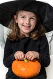 Happy Little Girl in Witch Costume Holding Pumpkin