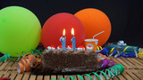 Chocolate birthday cake with candles burning on rustic wooden table with background of colorful balloons, gifts, plastic cups and streamers with black background