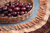 Ягоды вишни на плетеном подносе в окружении бахромы от бархатных штор.