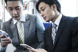 Two young businessmen have become addicted to smart phone on a train